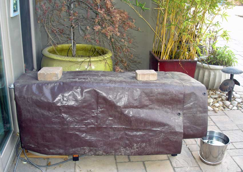 Outdoor cat houses covered by a tarp
