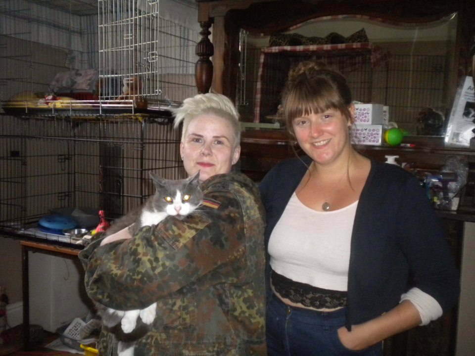 PIC FROM MERCURY PRESS (PICTURED: L-R: ZAPPA AND HER OWNER JULIE BLAIR WITH ANIMAL RESCUES AMY MERCER) A cat has been reunited with his owner 18 months after mysteriously crossing the Irish Sea. The grey-and-white moggy called Zappa was rescued in Speke Hall Road in Liverpool, Merseyside, on July 13 after a member of the public called charity Garston Animal Rescue to report him eating from takeaway bins. But staff at the rescue centre were dumbfounded when they scanned the micro-chip inside the cat and discovered that the feline was registered in Northern Ireland capital Belfast.