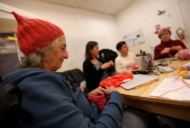 Claudia Miller, of Piedmont, knits a pussy hat while wearing one at Piedmont Yarn & Apparel in Oakland, Calif., on Wednesday, Jan. 18, 2017.