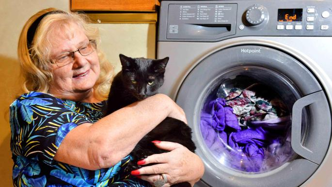 Mr Rae Sutton with her cat Tiggy who survived (just) a 30 minute wash in appliance