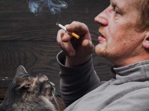 Man smoking with cat on lap