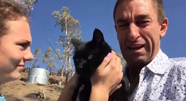 Man cries on being reunited with cat lost in fire