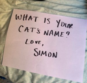 Simon's mom writes a sign to Theo's mom to open the dialogue on behalf of their cats.