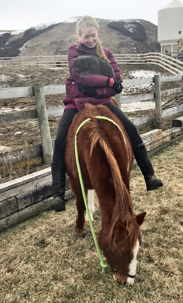 Girl holding cat while on horse