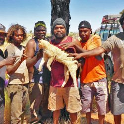 Aborigninal Australians with the feral cat they killed