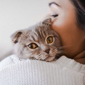 Woman cuddles a cat
