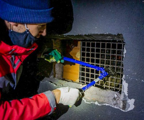 Man cuts hole in vetilation grill to apartment block leading to the basement