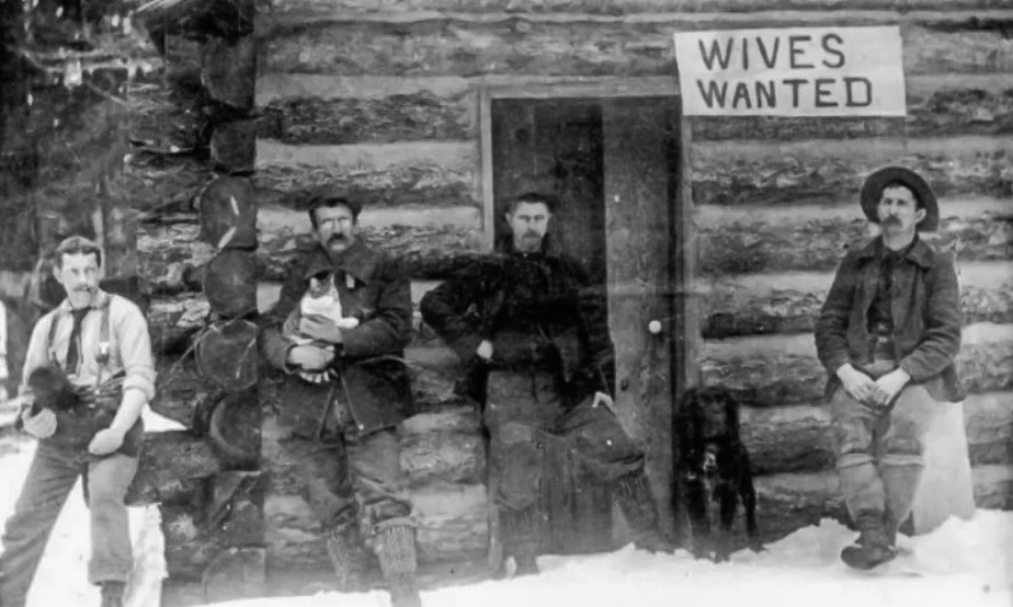 Four men looking for wives in 1913 with two of them holding cat companions and one has a a dog while the fourth has no companion animal