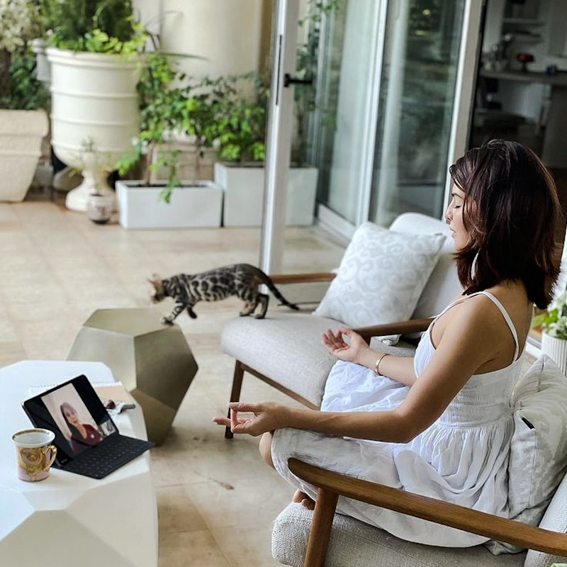 Jacqueline Fernandez in her apartment practising meditation with one of her cats a Bengal in the background