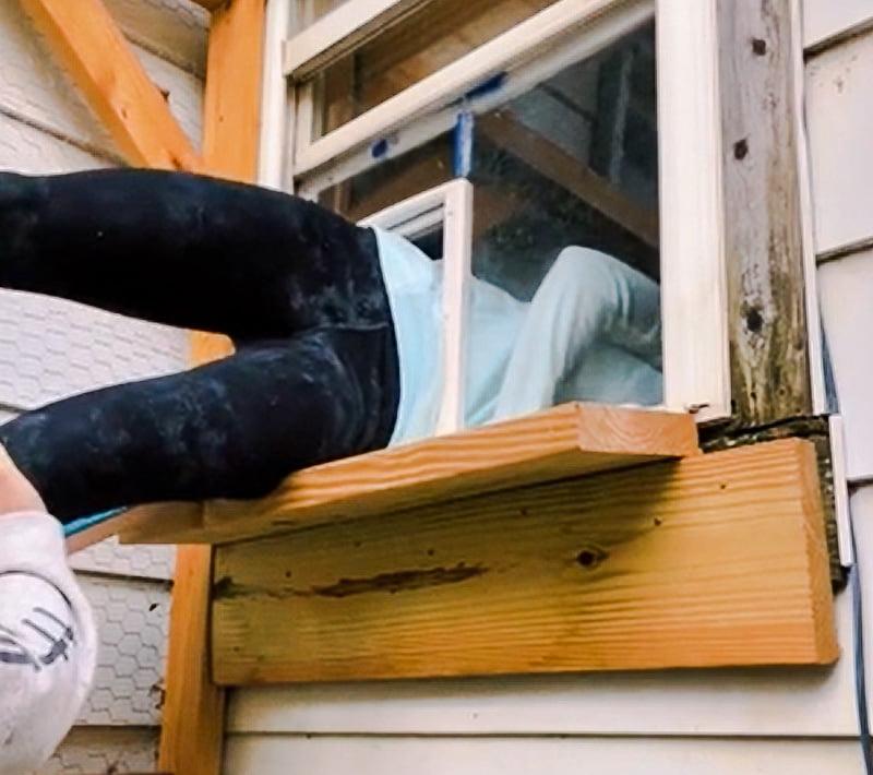 Woman climbs through a cat door in the US