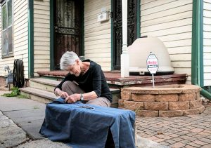 Barb Jones places a blanket over a cage containing a female feral cat to keep her calm