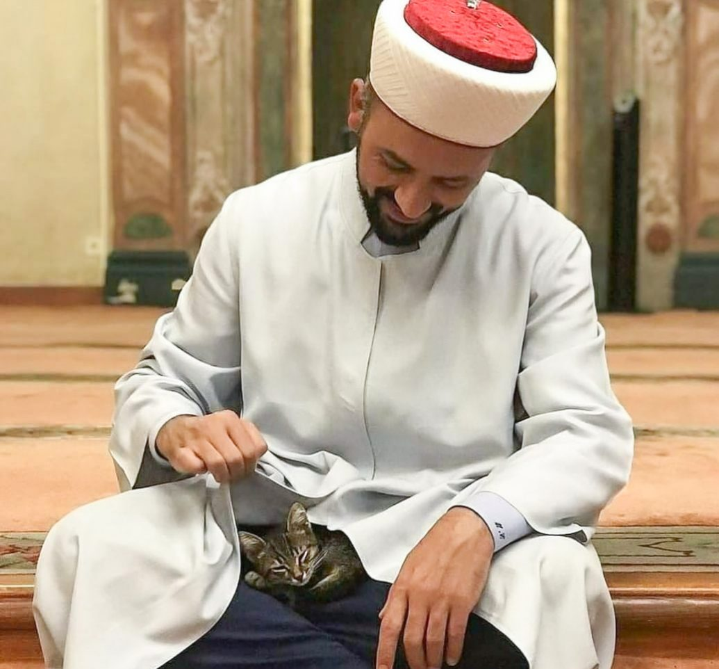 Imam Mustafa Efe with a kitten inside his mosque
